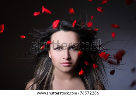 woman and flying leaves of red roses on a dark background