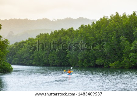 Woman and friends paddle on kayaks,Meeting sunset on kayaks.the tourist kayaking on the river with beautiful green nature view with mountains.Traveller on canoe or kayaker.