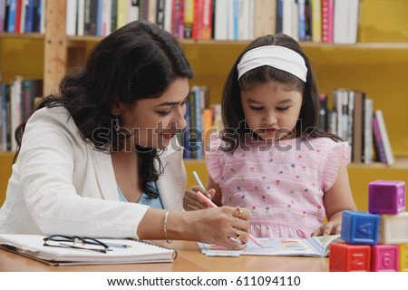 Woman and girl studying in library