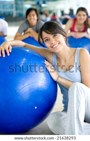 woman and group of people doing pilates in a gym