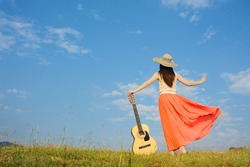 Woman and guitar standing on meadow with Cloud sky