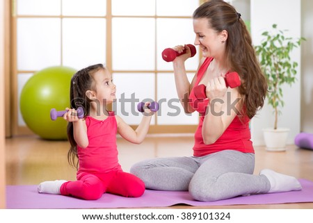 Woman and her child daughter doing fitness exercises  with dumbbells
