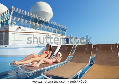 woman and her daughter both wearing swimsuit on chaise lounge