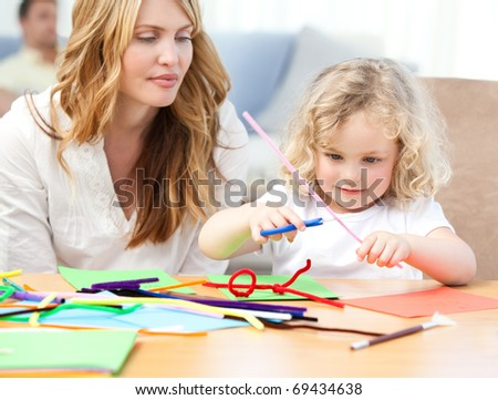 Woman and  her daughter cutting paper at home