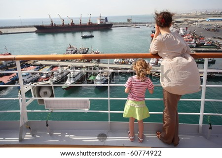 woman and her daughter standing and looking at ships in Qaboos Port.