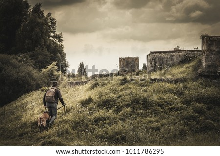 woman and her dog is heading for abandoned buildings. post apocalypse. stone walls