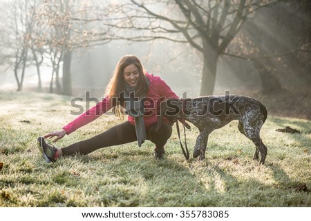 Woman and her dog stretching outdoor. Fitness girl and her pet working out together.