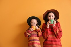 Woman and her little daughter with tasty cocoa drink on color background