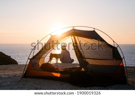 Woman and her pet dog sit at beach next to tent, solitude camping in nature. Sunset shot of young woman have self exploration time and connection to nature. Tranquility and mindfulness Imagine de stoc ©