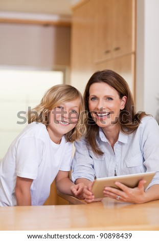 Woman and her son using tablet in the kitchen together