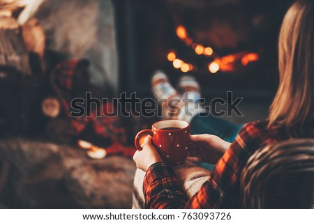Woman and her Teddy Bear by the fireplace. Unrecognisable relaxes by warm fire with a cup of hot drink and warming up her feet in woollen socks. Cozy atmosphere. Winter and Christmas holidays concept. #763093726