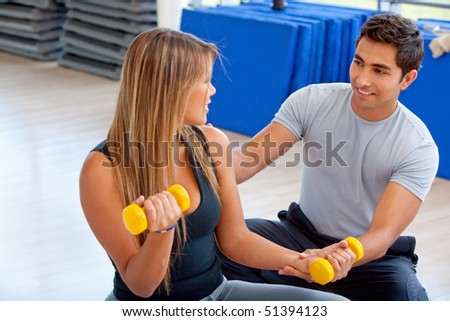 Woman and her trainer exercising at the gym