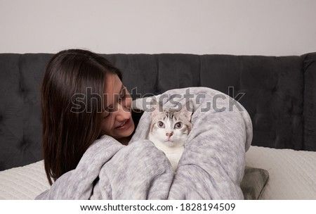 Woman and her white striped cat dressed like a baby wrapped in a gray blanket