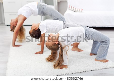 Woman and kids doing bridge stretch gymnastic exercises at home