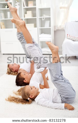 Woman and kids doing gymnastic exercises at home - closeup, focus on the first kid - stock photo