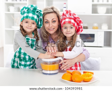 Woman and kids making fresh fruit juice - dressed as chefs in the kitchen