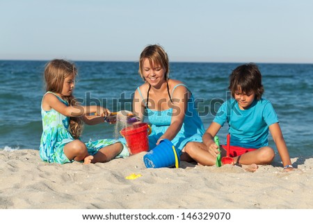 Woman and kids on the beach - playing with sand