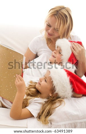 Woman and kids reading a tale at christmas time laying on the sofa