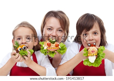 Woman and kids taking a bite from healthy and creative creature sandwiches - closeup
