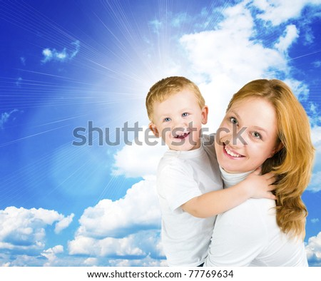 Woman and little boy against blue summer sky
