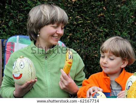 woman and little boy holding some halloween pumpkin with painted smiling face