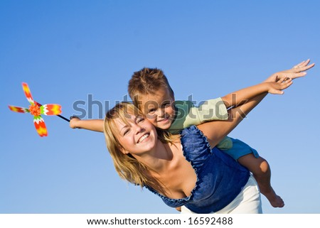 Woman and little boy playing airplane with a pinwheel against blue summer sky