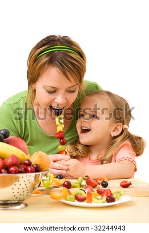 Woman and little girl eating fruit slices on a stick