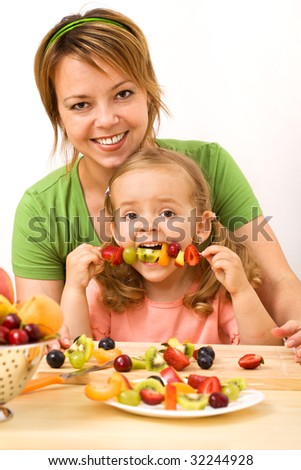 Woman and little girl eating fruit slices on a stick - healthy snack