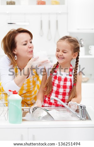 Woman and little girl having fun washing the dishes - playing with the foam