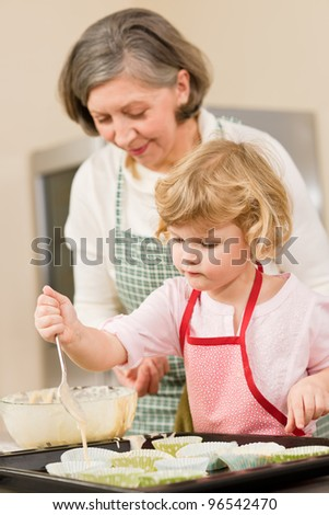 Woman and little girl make cupcakes together fill baking form