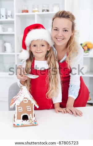 Woman and little girl making a gingerbread cookie house at christmas