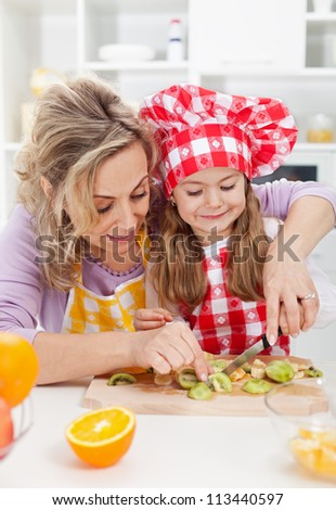 Woman and little girl making fresh fruits snack together - healthy eating concept - stock photo