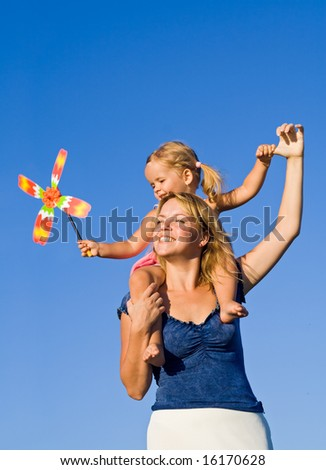 Woman and little girl playing outdoors with a propeller toy in the summer against blue sky