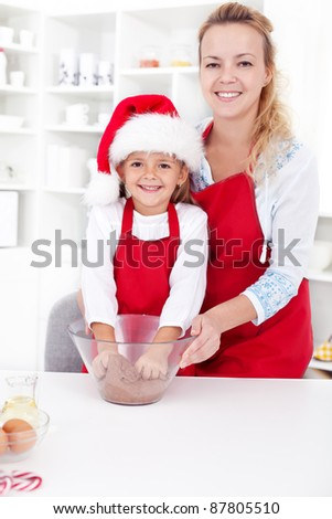 Woman and little girl preparing the christmas cookie dough together