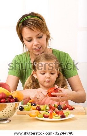 Woman and little girl slicing fruits preparing a healthy snack