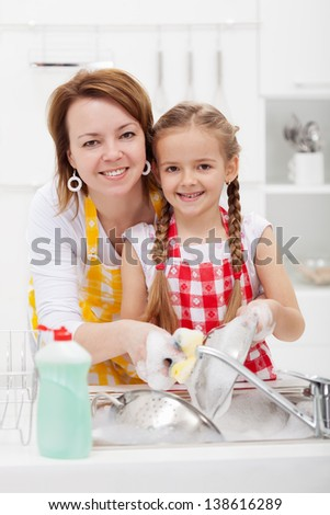Woman and little girl washing dishes in the kitchen together - stock photo