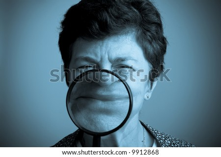 Woman and magnifier on her smile. Fake amused woman and psychology concept - stock photo