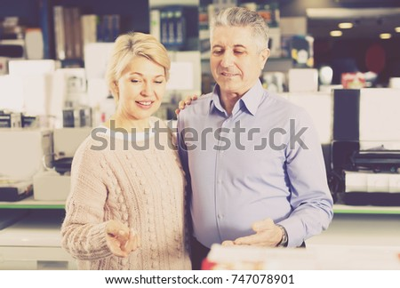 Woman and man are visiting shop of household appliances for survey of goods for kitchen and house.  #747078901
