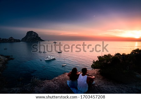 Woman and man back to the front watching a beautiful sunset at the beach. The beach is called Es Vedra, in Ibiza and belongs to balearic islands, in Spain Stok fotoğraf ©