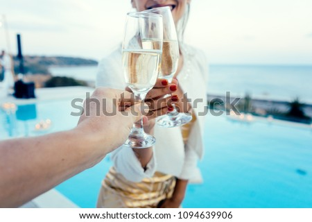 Woman and man clinking glasses at elegant pool party in summer
