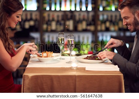 Woman and man eating good food in restaurant on evening
