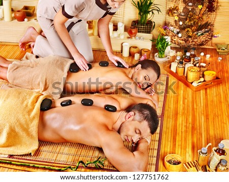 Woman and man getting stone therapy massage in bamboo spa.
