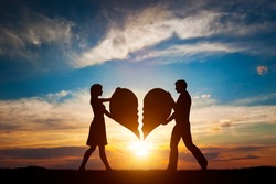 Woman and man holding two halves of broken heart going to be joined in one. Love conceptual.