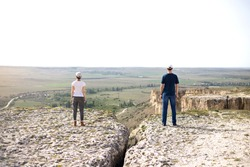 Woman and man in social distancing standing outdoors on the rock.