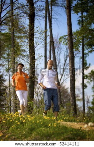 Woman and man jogging in forest with beautiful dandelions in foreground. - stock photo