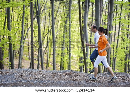 Woman and man jogging on gravel path beside each other with green beech forest in background. - stock photo
