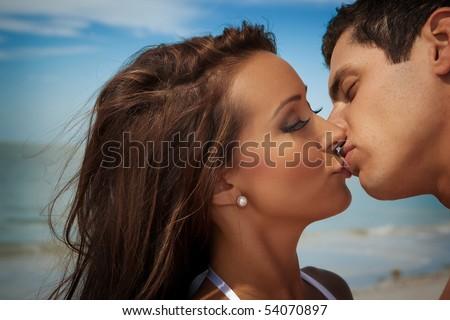Woman and man kissing at a beach