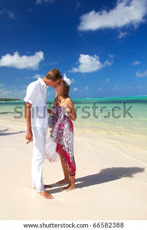Woman and man kissing on caribbean beach