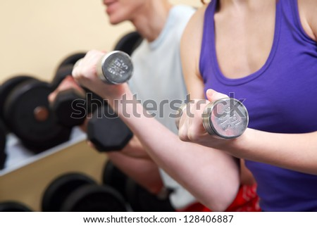 Woman and man lifting dumbbells doing biceps workout
