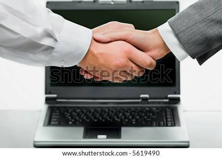 Woman and man shaking hands on the background of opened laptop